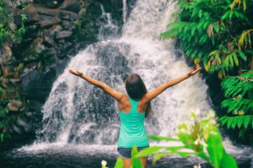 Hawaii travel nature waterfall woman hiker at Canyon Trail Waipoo Falls in Waimea, Kauai island, USA. Freedom happy girl with open arms meditating yoga in rainforest.