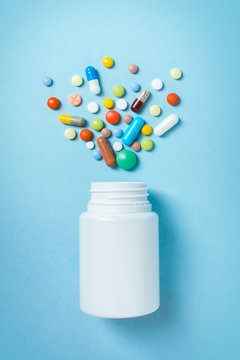 Assorted pharmaceutical medicine pills, tablets and capsules and bottle on blue background