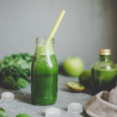 Healthy green smoothie with ingredients and ice cubes on gray background