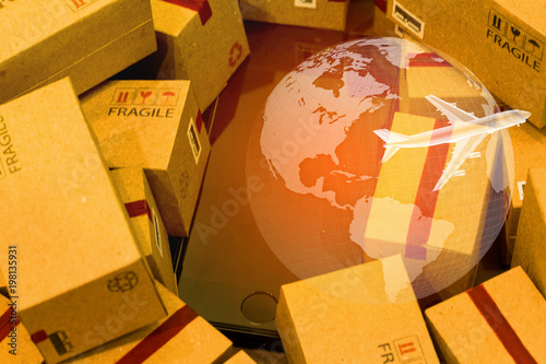 Black smartphone with World map on pile of cardboard boxes