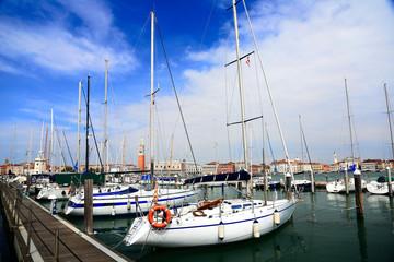 Boats parking by marina under blue sunny sky at San Giorgio Maggiore Island, Venice Italy