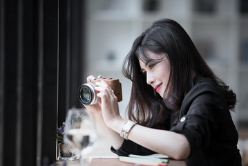 Beautiful woman in black suite holding camera ,looking at screen and taking photos