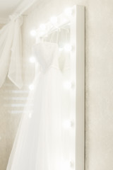 wedding dress hanging on the mirror, bride's morning