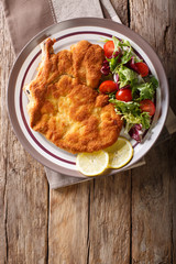 veal Milanese with lemon and fresh salad of tomatoes and lettuce close-up. Vertical top view