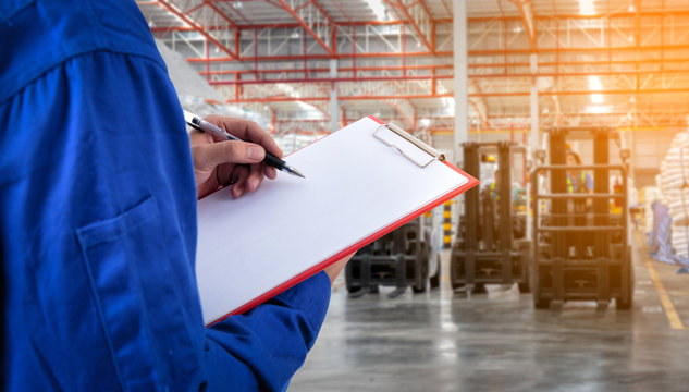 Worker checking document in front of the forklift at warehouse import export business.