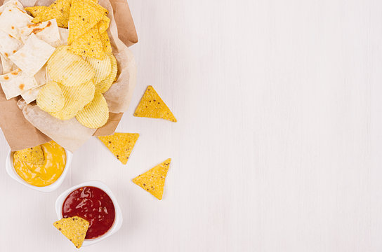 Golden different snacks on craft paper, triangles nachos, red and yellow sauce in bowl on soft white wood background, with copy space, border. Summer fresh fast food background.
