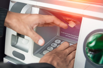 Close-up of hand businessman entering PIN/pass code on ATM/bank machine keypad