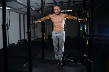 Handsome man athlete training at gymnastic rings