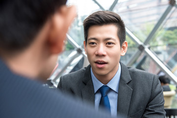Young handsome Asian Chinese businessman talking to his partner