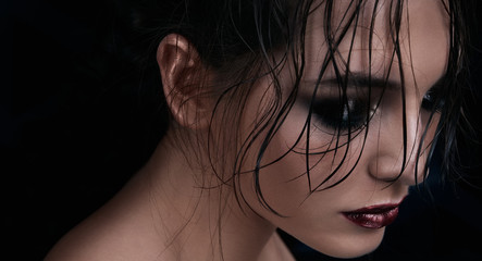 Beautiful girl with wet hair and bright dark makeup looking down. Beauty concept.