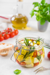 marinated feta cheese with olive oil, spicy herbs, garlic and chili pepper in jar
