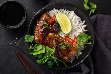 bowl of teriyaki chicken wings and rice served with lime, cilantro and sesame seeds