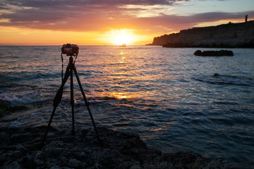 Camera on a tripod on the sea beach during a beautiful fiery sunset