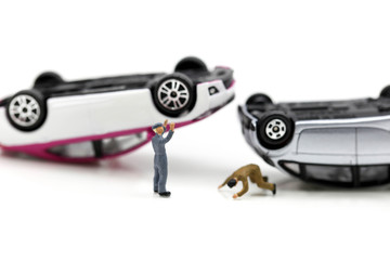 Miniature people : people with car crash accident damaged.