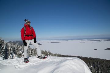 Snowshoe hiker on the Paha-Koli peak enjoys the winter landscape