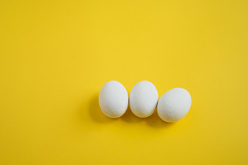 three white wooden eggs on yellow background, Easter holidays decoration