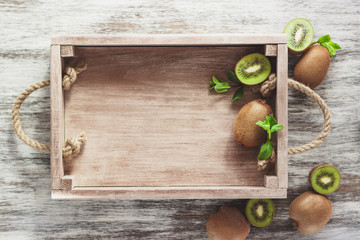 Green kiwis and mint leaves in the wooden tray