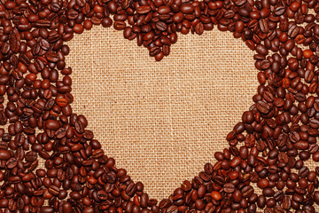 Frame on the background of a baggy cloth lined with coffee beans in the form of a heart