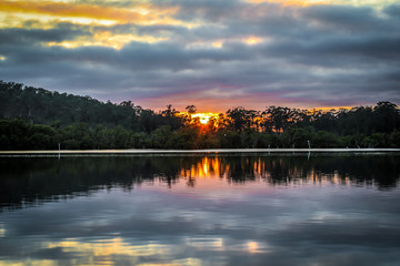 Sun rising over country river with colourful sky reflected in water