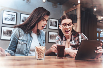 Look at this. Happy nice excited woman sitting with her friend and holding a tablet while showing her an interesting picture