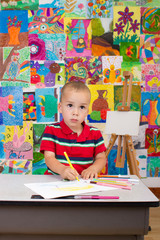 Little artist. Colorful wall with paintings in background.