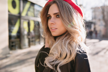 Beautiful fashion girl with long blond hair dressed leather jacket and red hat walks on the street in sunlight with happy true emotions. Background the city
