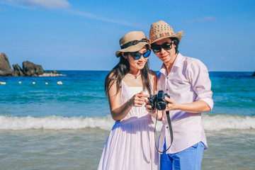 Asia couple love on the beach.a man and a woman looking for picture on camera near the sea on vacation.couple travelers enjoying holiday.