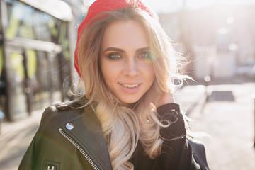 Adorable woman with big green eyes and wavy long hair dressed leather jacket and red hat smiles to the camera and enjoys good weather. Outside portrait of stylish modern girl