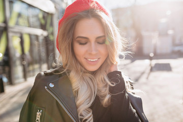 Close-up portrait of charming pretty woman with long blond hair dressed in black jacket and red hat closes her eyes and smiles of fantastic smile on the sunny street