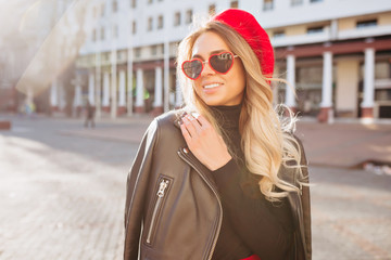Happy girl with long wavy hair dressed red hat and fashion red glasses walks in sunlight in the city with happy smile and enjoy life