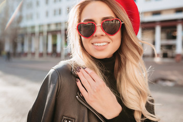 Close-up portrait of fashionable blonde woman in red hat and stylish sunglasses walking in the street. Fashion spring summer photo of adorable woman