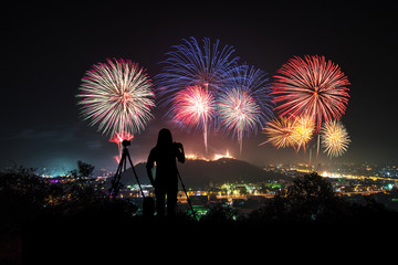 couple photographer looking at the firework display on top of the mountain in firework festival on holiday.Phanakornkiri Petchaburi Thailand.