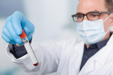 Ein Arzt mit Mundschutz hält eine Blutprobe in der Hand