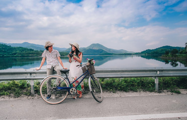 couple traveler standing beside bicycle and happy for view of nature near the lake  on vacation background is mountain.