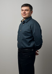 man portrait dressed in dark shirt and black pants over gray background