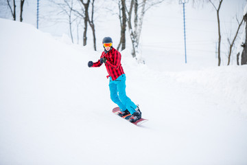 Image of sportive snowboarder man riding on snowy hill