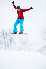Picture of sportive man snowboarder jumping on snowy hill