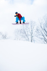 Image of athlete wearing helmet with snowboard jumping in snowy resort