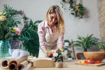 Portrait of florist composing bouquet at table on background of flowers