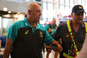 Australian cricket coach Darren Lehmann walks through a police cordon at Cape Town International Airport