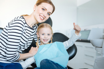 Perfect mood. Loving young mother hugging her little daughter and posing for the camera together with her while the girl sitting in the dentist chair and waiting for a checkup