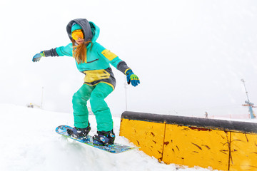 Young snowboarder jumping on ramp.