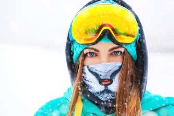 Happy young snowboarder girl in snowboard goggles.