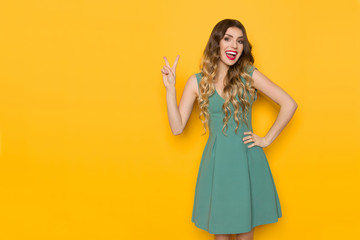 Laughing Woman In Green Mini Dress Is Showing Peace Hand Sign
