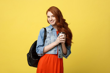 Happy young woman with a disposable coffee cup over isolated bright yellow background.