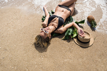 happy woman lays on the sand on exotic beach