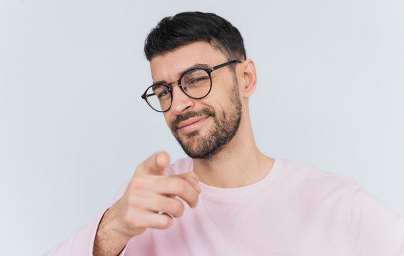 Studio portrait of pleased male wears pink sweater, points at you, chooses someone or advertises product. Handsome smiling man indicates at camera, isolated over white wall background