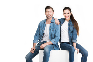 happy couple sitting on white cube and looking at camera, isolated on white