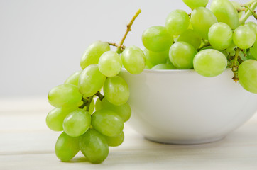 White grapes. A branch of grapes in a white bowl on white background.