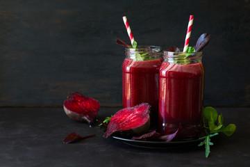 Fresh beetroot smoothie, beet, arugula and lettuce leaves on dark wooden background